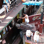 A deckhand ensures that one Junk's windows are not broken by another Junk's dragon