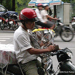 Birthday? Engagement? Grandma's coming home from hospital? Cake, flowers and wallet are easy to manage for a seasoned Hanoi moped rider